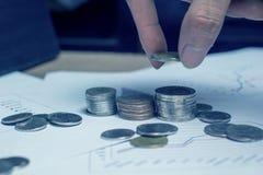 Übergeben Sie das Halten der Münze in Stapelgeld oder -münze Stockbilder