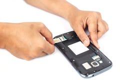 Übergeben Sie das Halten der SIM-Karte und setzen Sie sich in den Smartphone, der auf Weiß lokalisiert wird Lizenzfreies Stockbild
