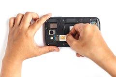 Übergeben Sie das Halten der SIM-Karte und setzen Sie sich in den Smartphone, der auf Weiß lokalisiert wird Stockbild