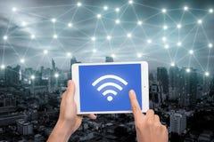 Übergeben Sie das Halten der Tablette mit wifi Ikone auf Stadt und Netz connectio Lizenzfreies Stockbild