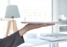 Übergeben Sie das Halten der Tablette nahe bei stilvollem Raum mit Lampe Stockbild