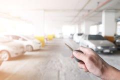 Übergeben Sie das Halten des Autoschlüssels im Parken, mit orange Licht Lizenzfreie Stockfotografie