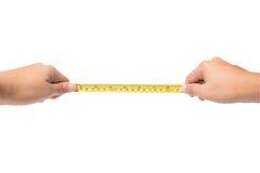 Übergeben Sie das Halten des Bandpatronenmeters lokalisiert auf Weiß stockfotografie