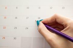 Übergeben Sie das Halten des Bleistifts auf Kalender für die Herstellung von Verabredung importa Stockbild