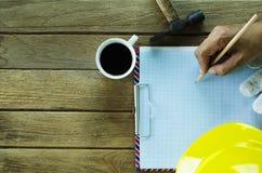 Übergeben Sie das Halten des Bleistifts auf Zeichenpapiers- mit Maßeinteilungblatt und Kaffeetassen hämmern, stockfoto