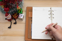 Übergeben Sie das Halten des Bleistiftschreibens auf Notizbuch- und Weihnachtsdekoration Stockfotos