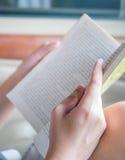 Übergeben Sie das Halten des Buches, um beim Sitzen zu lesen in einem Auto Lizenzfreies Stockbild