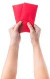 Übergeben Sie das Halten des chinesischen roten Umschlags mit dem Geld, das über weißem Hintergrund lokalisiert wird Stockbild