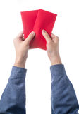 Übergeben Sie das Halten des chinesischen roten Umschlags mit dem Geld, das über weißem Hintergrund lokalisiert wird Stockfotos