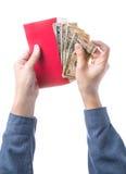 Übergeben Sie das Halten des chinesischen roten Umschlags mit dem Geld, das über weißem Hintergrund lokalisiert wird Stockbilder
