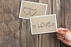 Übergeben Sie das Halten des Fotos mit Textliebe auf Sand und dem Foto mit zwei Herzen auf Sand auf Weinleseschmutz hölzernem bac Stockfotografie