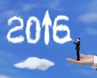 Übergeben Sie das Halten des Geschäftsmannes, der Pfeil 2016 herauf Wolken mit Himmel spritzt Lizenzfreies Stockfoto