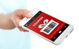 Übergeben Sie das Halten des Handys mit Weihnachtskupon über Weiß Lizenzfreies Stockfoto