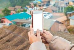 Übergeben Sie das Halten des Handys, um die Fotoansicht der Stadt zu vertreten Stockfotos