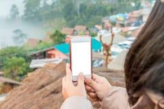 Übergeben Sie das Halten des Handys, um die Fotoansicht der Stadt zu vertreten Stockfotografie