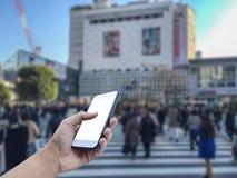 Übergeben Sie das Halten des intelligenten Mobiltelefons mit einer Menge von Leuten in Shibuy Stockfoto