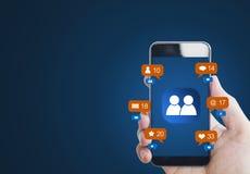 Übergeben Sie das Halten des intelligenten Mobiltelefons, mit Mitteilungsikonen und Online-Community-Ikone auf Schirm stockbild