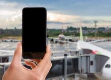 Übergeben Sie das Halten des intelligenten Mobiltelefons mit schwarzem Schirm auf Flughafenhintergrund Stockbild