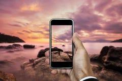 Übergeben Sie das Halten des intelligenten Telefons, das Foto der Sonnenunterganglandschaft in der vertikalen Zusammensetzung, in Stockbild