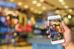 Übergeben Sie das Halten des intelligenten Telefons, das Foto von unscharfen bokeh Lichtern macht Stockbilder