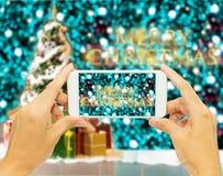 """Übergeben Sie das Halten des intelligenten Telefons für nehmen Foto """"Merry Weihnachten-"""" Lizenzfreies Stockfoto"""