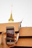 Übergeben Sie das Halten des intelligenten Telefons (Handy) mit Pagode und Tempel r Lizenzfreie Stockfotos