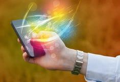 Übergeben Sie das Halten des intelligenten Telefons mit abstrakten glühenden Linien Stockfotos