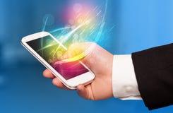 Übergeben Sie das Halten des intelligenten Telefons mit abstrakten glühenden Linien Lizenzfreie Stockfotografie