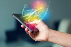 Übergeben Sie das Halten des intelligenten Telefons mit abstrakten glühenden Linien Lizenzfreies Stockbild