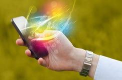 Übergeben Sie das Halten des intelligenten Telefons mit abstrakten glühenden Linien Stockbilder