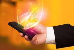 Übergeben Sie das Halten des intelligenten Telefons mit abstrakten glühenden Linien Stockbild