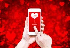 Übergeben Sie das Halten des intelligenten Telefons mit dem Senden des Liebeswortes und der Herzform Stockbilder