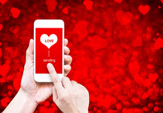 Übergeben Sie das Halten des intelligenten Telefons mit dem Senden des Liebeswortes und der Herzform Lizenzfreie Stockbilder