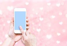 Übergeben Sie das Halten des intelligenten Telefons mit schwarzem Schirm auf rosa Pastellherzen Stockfotografie