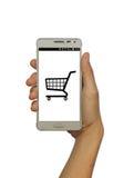 Übergeben Sie das Halten des intelligenten Telefons mit Warenkorb auf lokalisiertem weißem Hintergrund Lizenzfreie Stockbilder