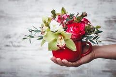 Übergeben Sie das Halten des kleinen roten Vase mit Blumenstrauß von Blumen auf grauem Raum für Text Stockfoto