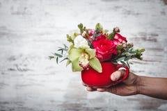 Übergeben Sie das Halten des kleinen roten Vase mit Blumenstrauß von Blumen auf grauem Raum für Text Stockfotos