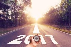 Übergeben Sie das Halten des Kompassses auf leerer Asphaltstraße und Konzept 2017 des neuen Jahres Stockbilder