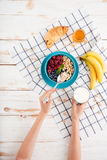 Übergeben Sie das Halten des Löffels mit Getreidefrühstück und Schale Milch Stockbild