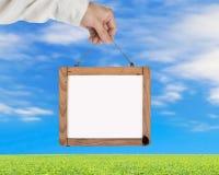 Übergeben Sie das Halten des leeren weißen Anschlagbretts mit Himmelwolkengras Stockfotos