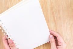 Übergeben Sie das Halten des leeren weißen offenen Buches über Holzschreibtisch, Spott herauf Temp Lizenzfreie Stockfotografie