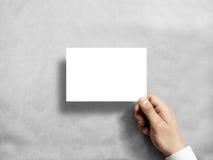 Übergeben Sie das Halten des leeren weißen Postkartenfliegers in stockfotografie