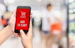 Übergeben Sie das Halten des Mobiles hinzufügen Warenkorbprodukt, um mit online zu kaufen stockfoto