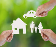 Übergeben Sie das Halten des Papierhauses, Auto, Familie auf grünem Hintergrund Stockfotos
