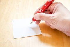 Übergeben Sie das Halten des roten Stiftes mit dem weißen Herzmuster und auf freien Raum schreiben Lizenzfreie Stockfotos
