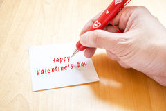 Übergeben Sie das Halten des roten Stiftes mit dem weißen Herzmuster und auf freien Raum schreiben Lizenzfreies Stockfoto