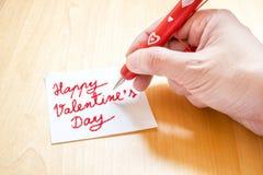 Übergeben Sie das Halten des roten Stiftes mit dem weißen Herzmuster und auf freien Raum schreiben Stockbild