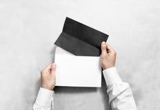 Übergeben Sie das Halten des schwarzen leeren Umschlags und des gefalteten Broschürenmodells Lizenzfreie Stockfotografie