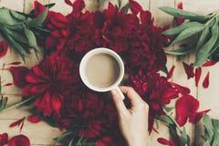 Übergeben Sie das Halten des stilvollen Kaffees und der schönen roten Pfingstrosen auf rustikalem Stockbild