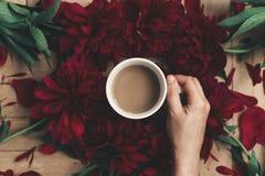Übergeben Sie das Halten des stilvollen Kaffees und der schönen roten Pfingstrosen auf rustikalem Stockfotografie